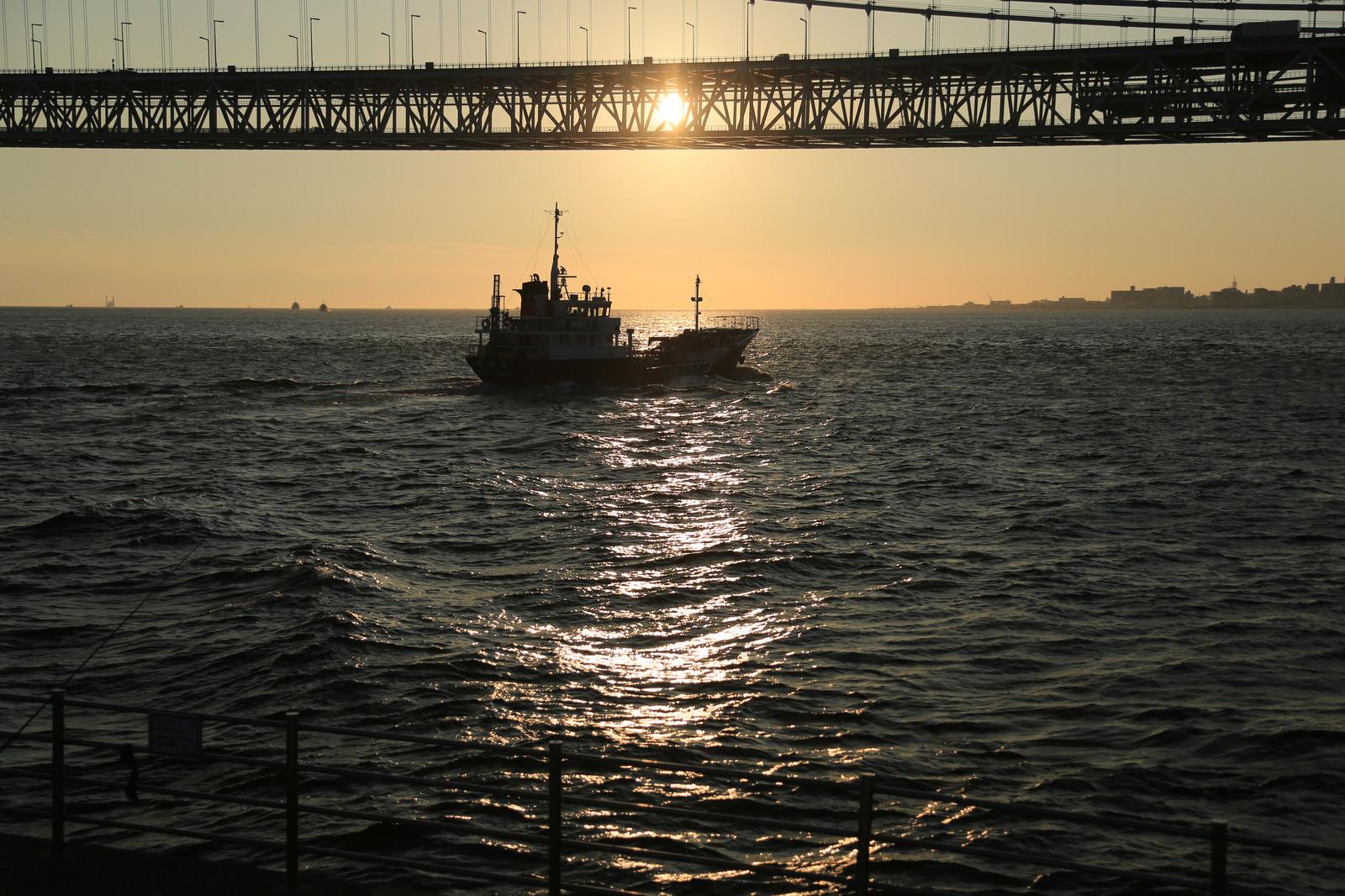 「夕焼けと小型船のシルエット」の写真