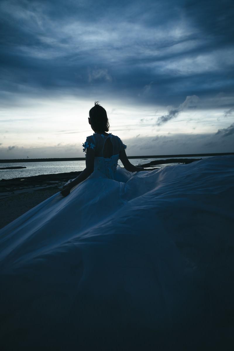 「浜辺でウェディングドレスを着た女性」の写真