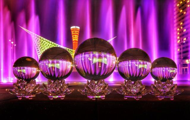 ライトアップされた噴水を映し込む水晶玉の写真