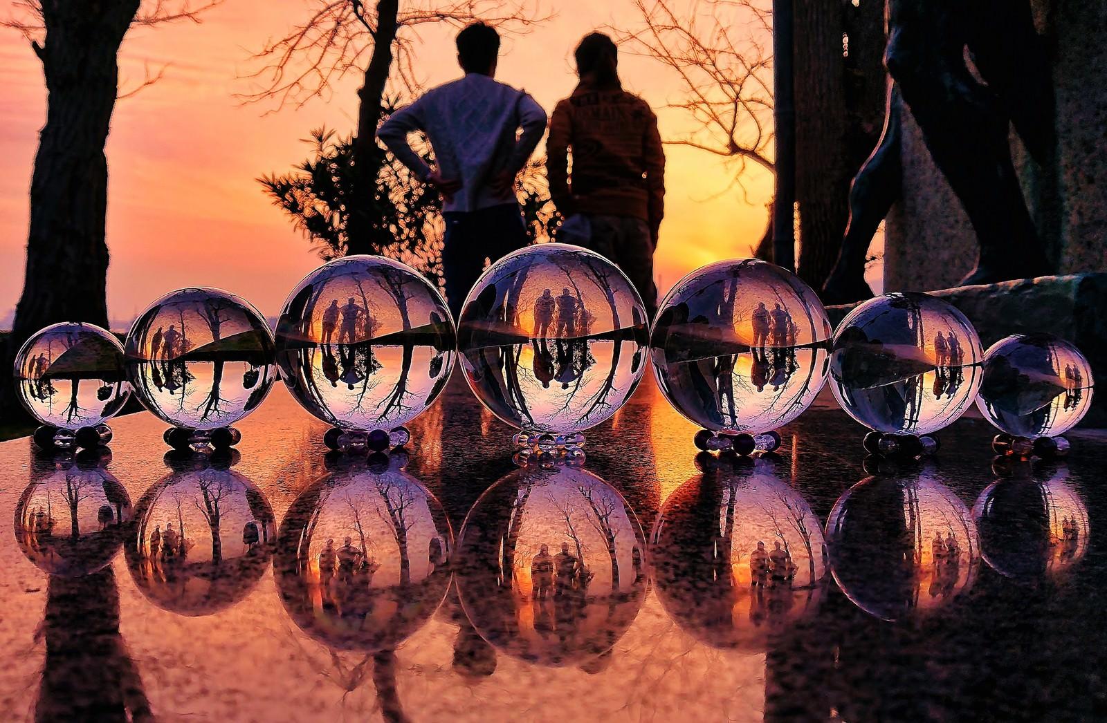 「ガラス玉越しの夕焼けと二人組のリフレクション」の写真