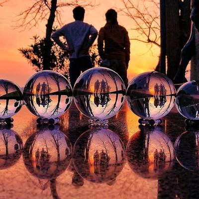 ガラス玉越しの夕焼けと二人組のリフレクションの写真