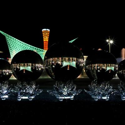 ガラス玉の中に反転する神戸の夜景の写真