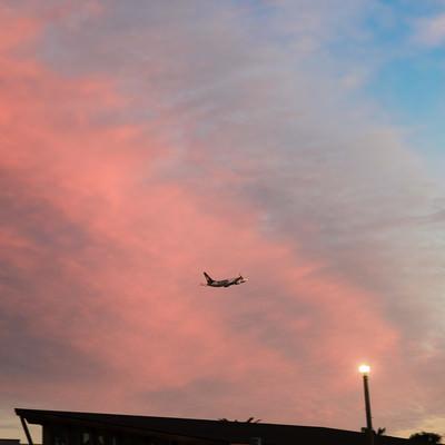 夕焼け雲と飛び立つ旅客機の写真