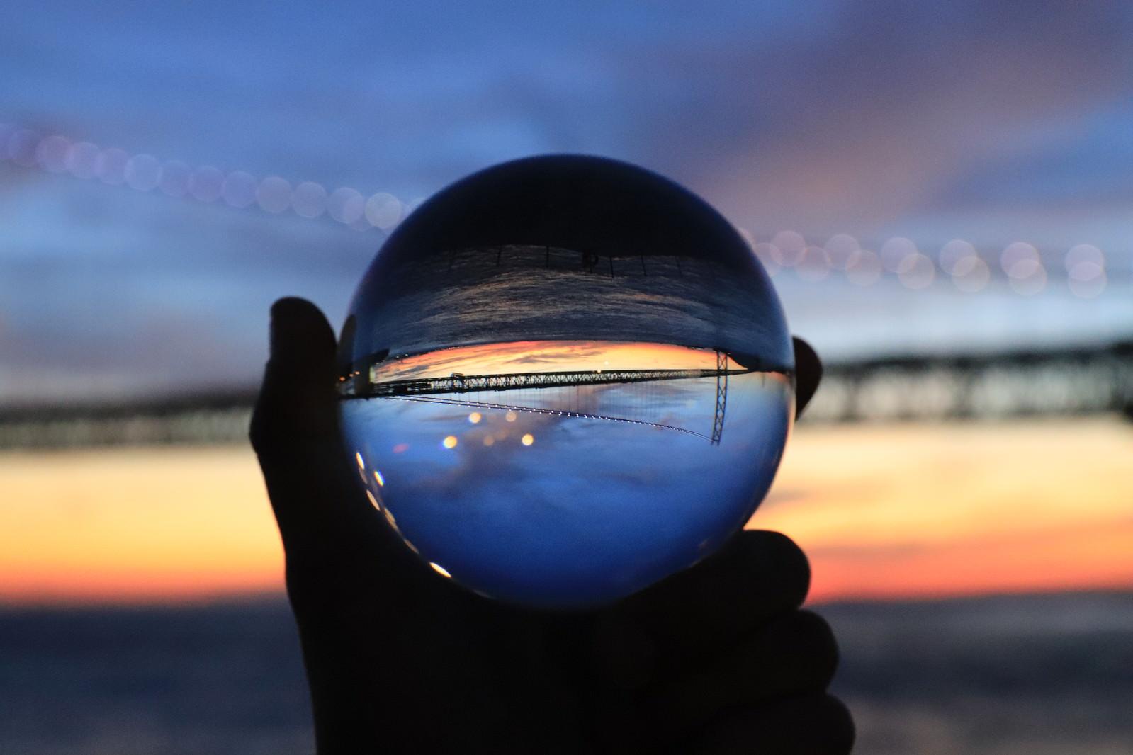 「ガラス玉越しに見た夕焼けと橋」の写真