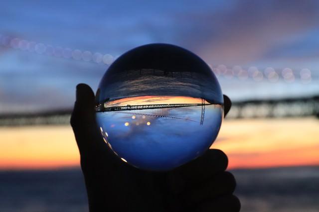 ガラス玉越しに見た夕焼けと橋の写真