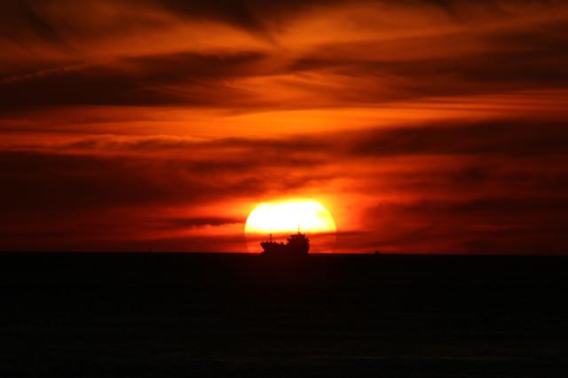 夕日に染まる空と貨物船のシルエットの写真