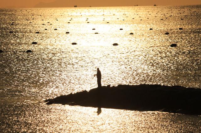 夕焼けにきらめく海と釣り人の写真