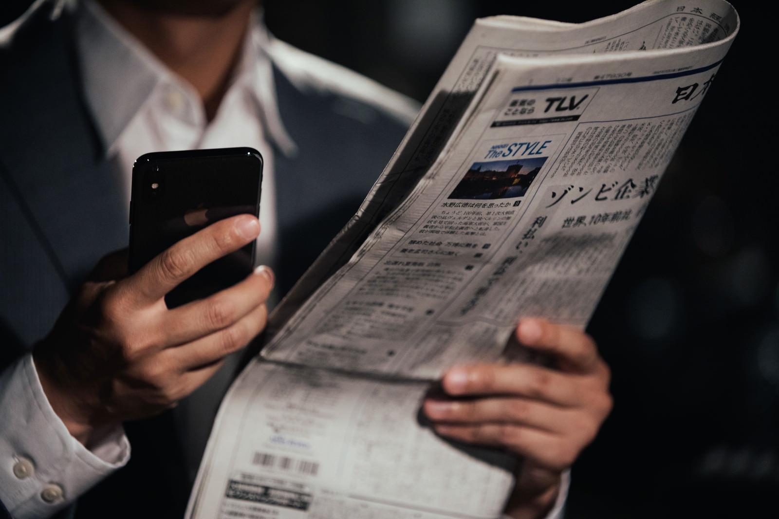 「紙面を読んで急いで検索するビジネスマン」の写真[モデル:大川竜弥]