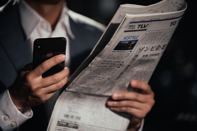 紙面を読んで急いで検索するビジネスマンの写真