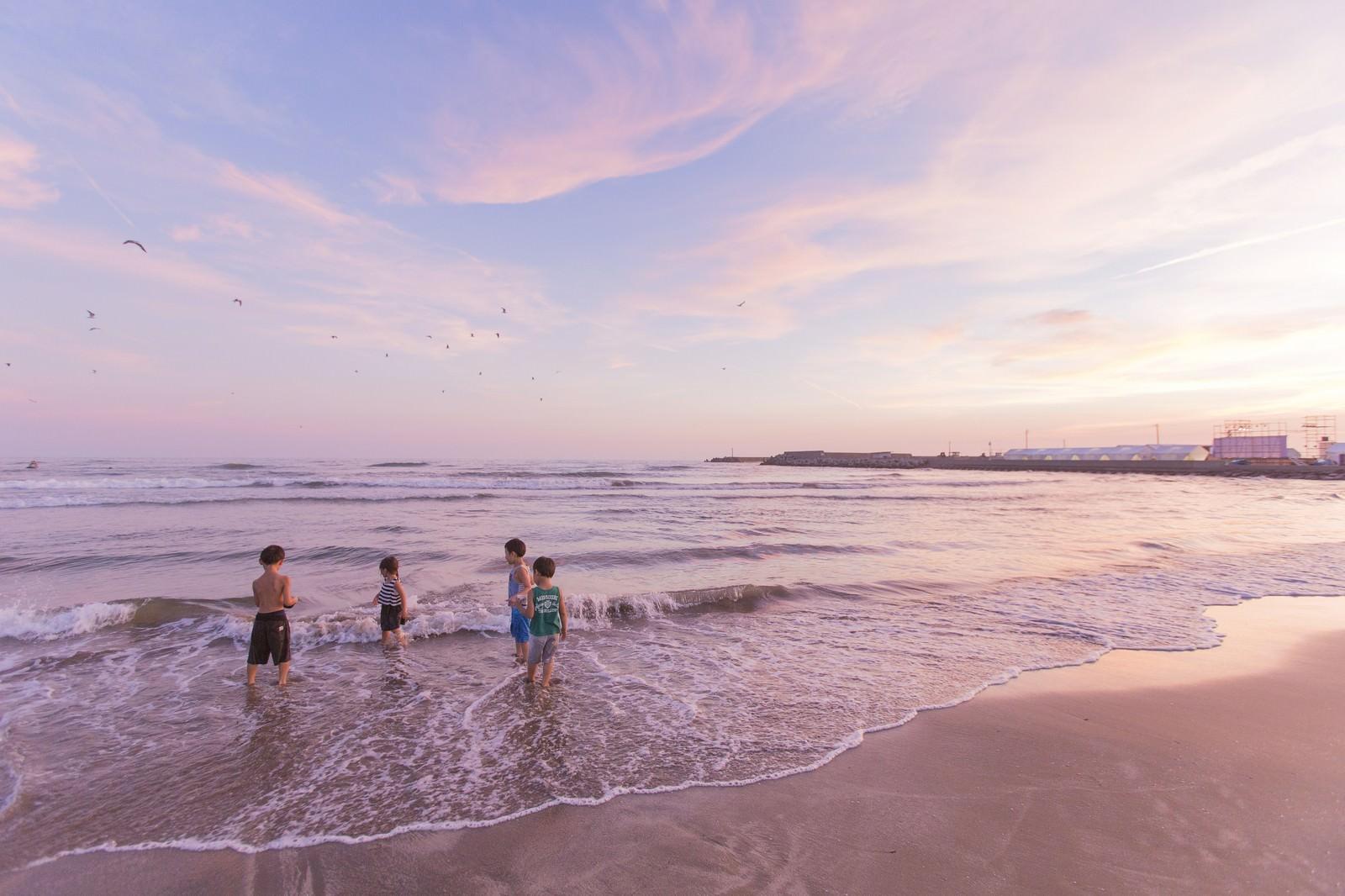 「夕暮れに浜辺で遊ぶ子どもたち」の写真