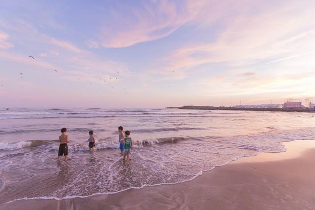 夕暮れに浜辺で遊ぶ子どもたちの写真