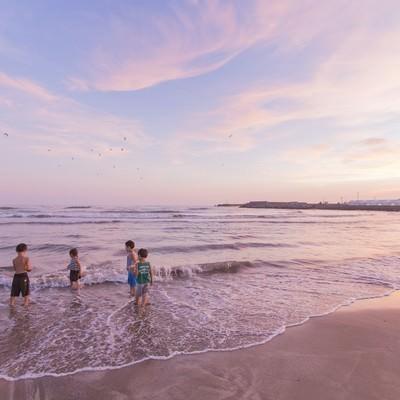 「夕暮れに浜辺で遊ぶ子どもたち」の写真素材