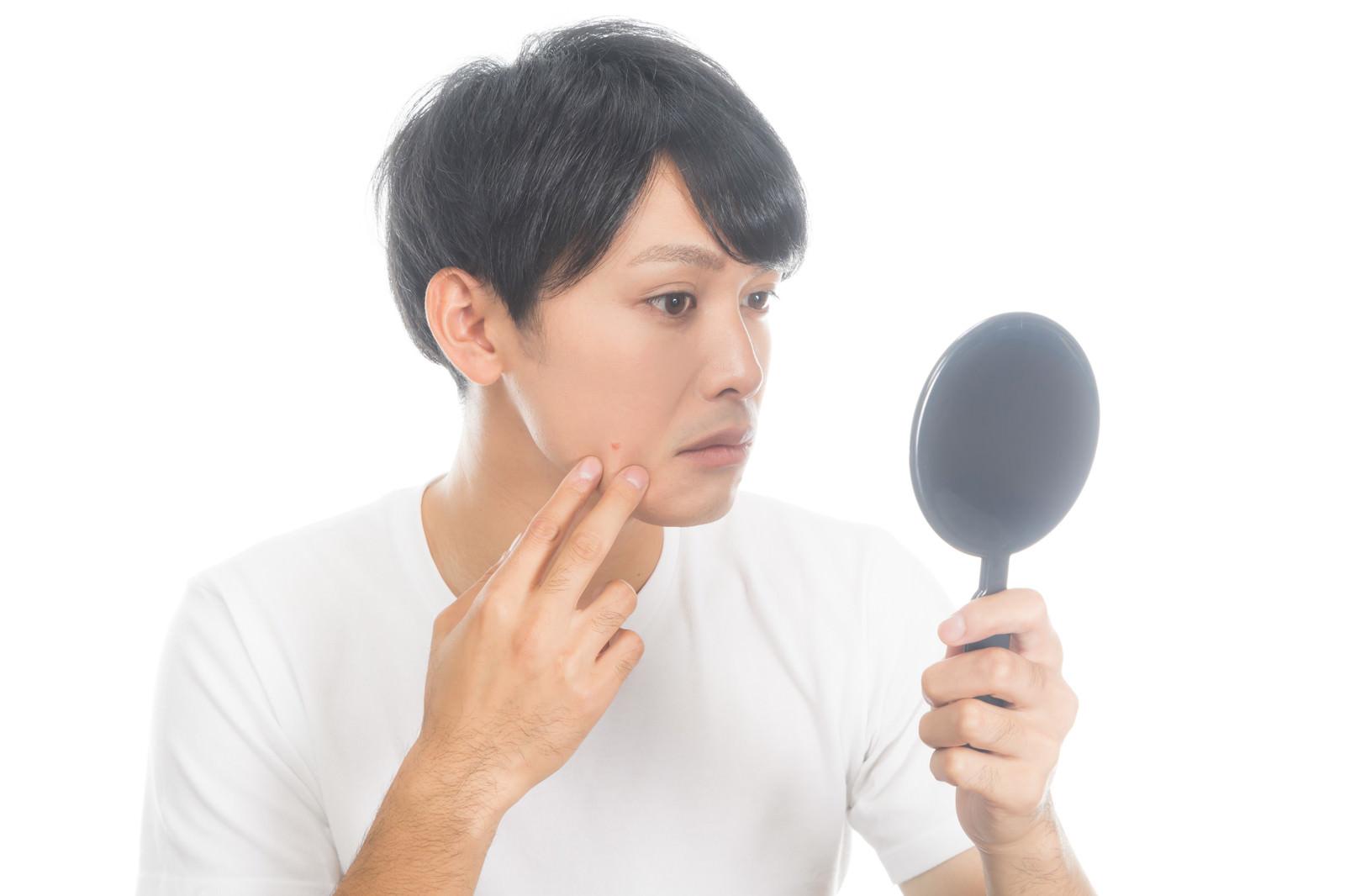 「手鏡で肌チャックを欠かさない男性」の写真[モデル:完伍]
