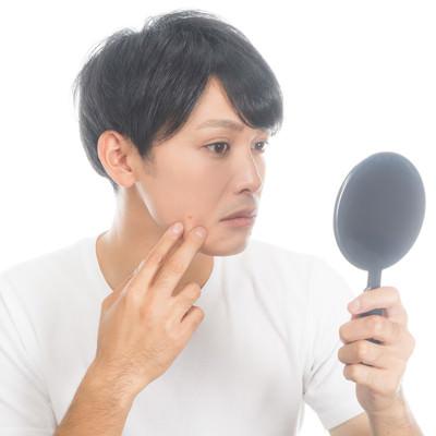 「手鏡で肌チャックを欠かさない男性」の写真素材
