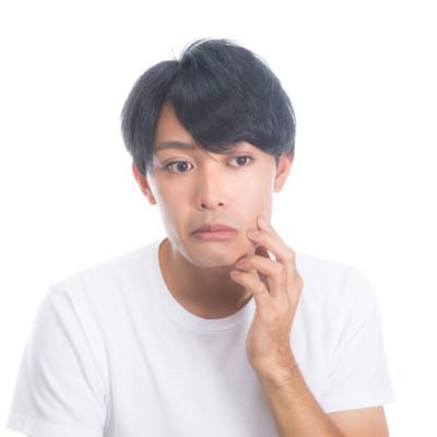 「顔のハリ具合を気にする男性」の写真素材