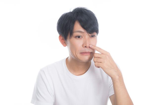 鼻頭にできる吹き出物(面疔)を気にする男性の写真