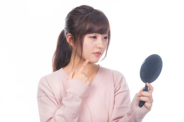 手鏡でニキビを確認する若い女性の写真