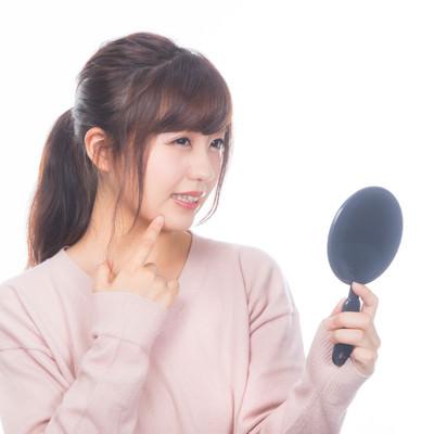 「手鏡で吹き出物を見る女性」の写真素材
