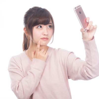 「手鏡のかわりに内向きカメラで確認する女性」の写真素材