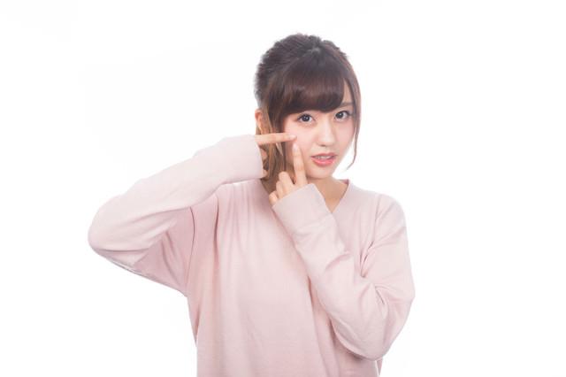 指でニキビを潰したくなる女性の写真