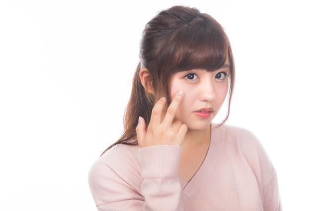 顔の肌荒れを気にする若い女性の写真