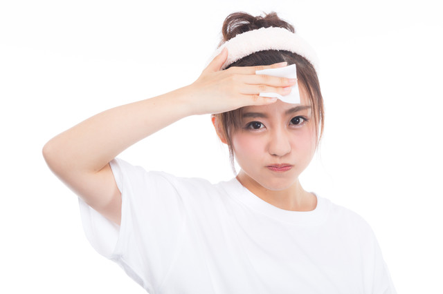 額のメークを落とす女性の写真