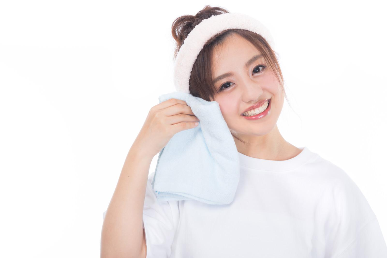 「柔らかいタオルを頬にあてる女性」の写真