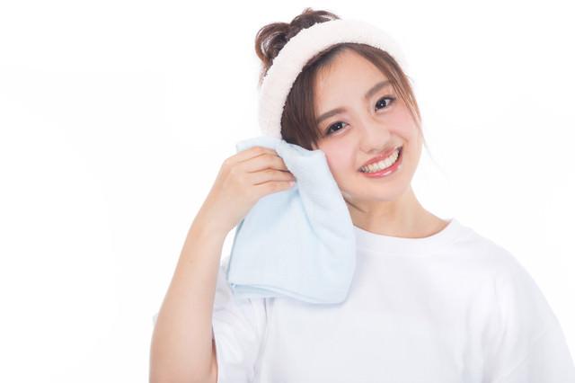 柔らかいタオルを頬にあてる女性の写真