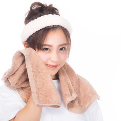 「タオルで顔を拭う女性」の写真素材