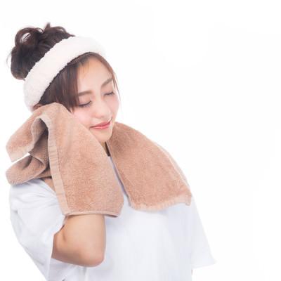 「タオルで頬を覆う女性」の写真素材
