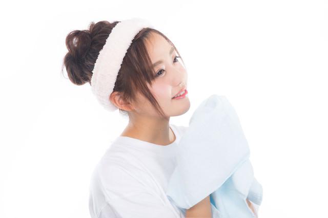 爽やかな朝にタオルを持って顔を洗う女性の写真