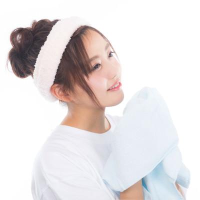 「爽やかな朝にタオルを持って顔を洗う女性」の写真素材