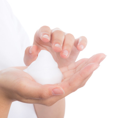 「クレンジング用の泡を持つ女性の手」の写真素材