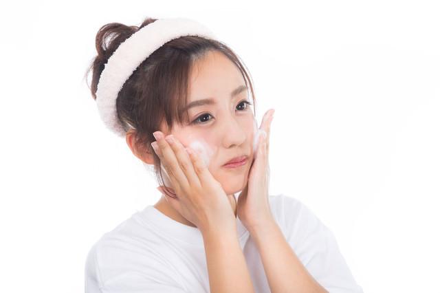 クレンジングの泡で洗顔中の女性の写真