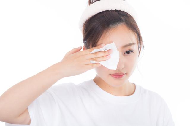 目元の化粧を落とす若い女性の写真