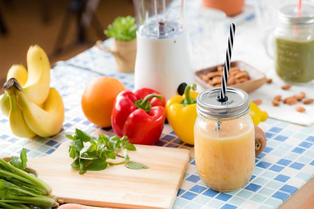 テーブルの上にあるスムージーと緑黄色野菜の写真