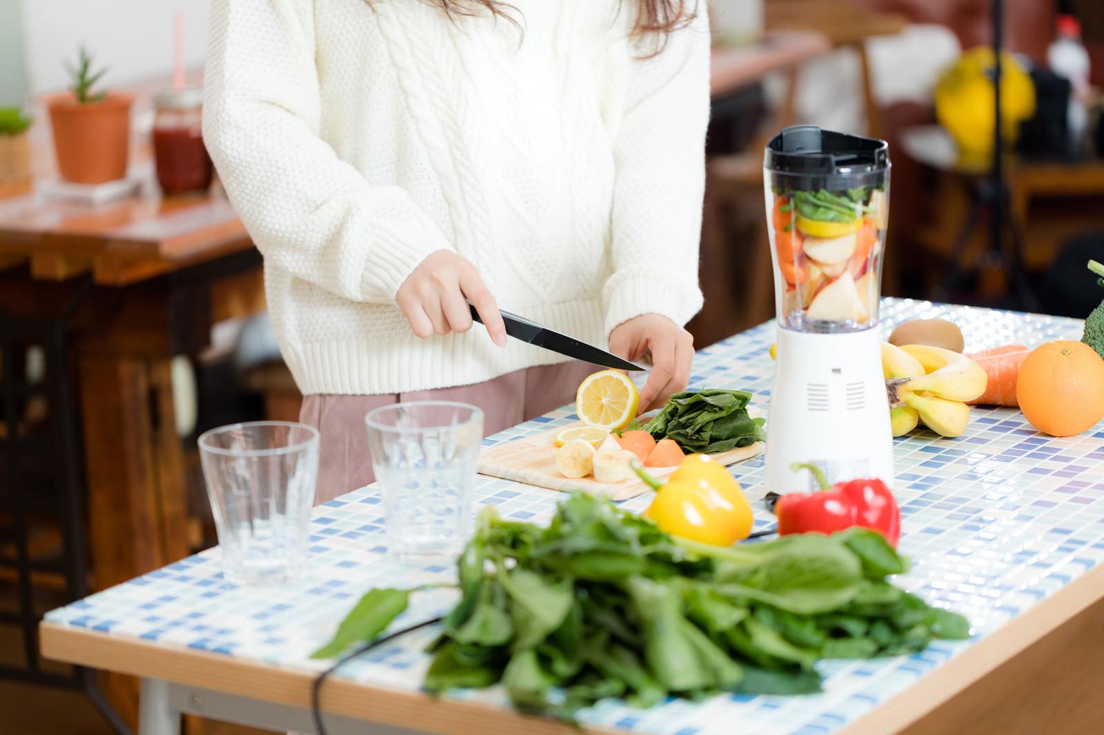 「スムージー用に果物をカットする女性」の写真