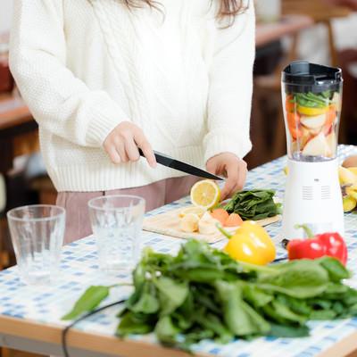 「スムージー用に果物をカットする女性」の写真素材