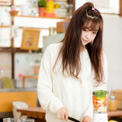 「ジューサーに入るサイズに果物や野菜をカットするスムージー女子」の写真素材