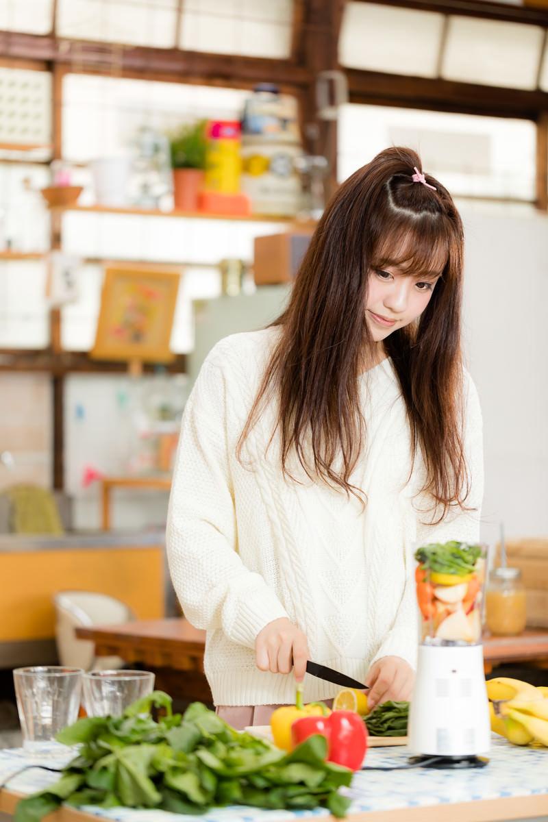 「ジューサーに入るサイズに果物や野菜をカットするスムージー女子」の写真[モデル:河村友歌]