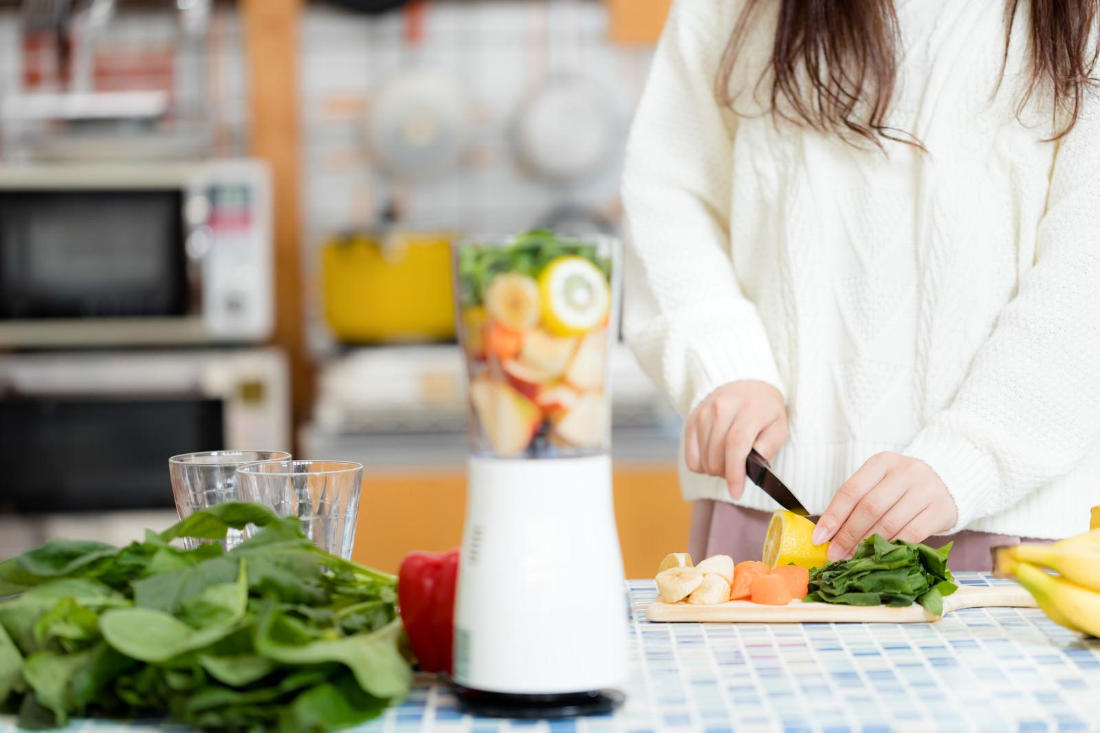「キッチンでスムージー用の野菜をカットする女性」の写真