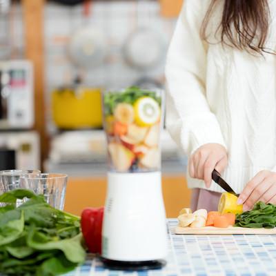 キッチンでスムージー用の野菜をカットする女性の写真