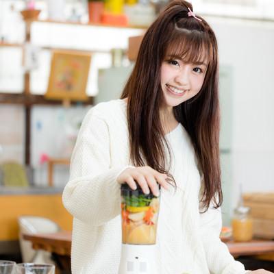 「ミキサーに野菜や果物を入れてスムージーを作る女子」の写真素材