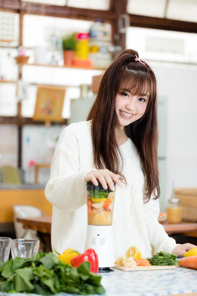 「ミキサーに野菜や果物を入れてスムージーを作る女子」の写真[モデル:河村友歌]