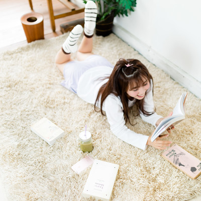「グリーンスムージーを飲みながら本を読む部屋着女子」の写真素材