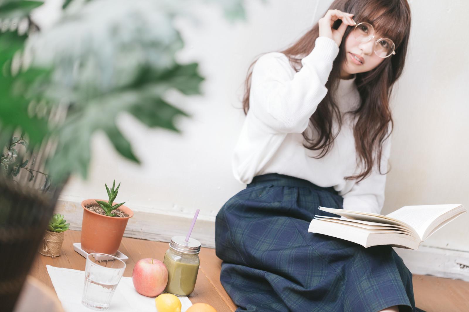 「読書しながらグリーンスムージーを側に置く女性」の写真[モデル:河村友歌]