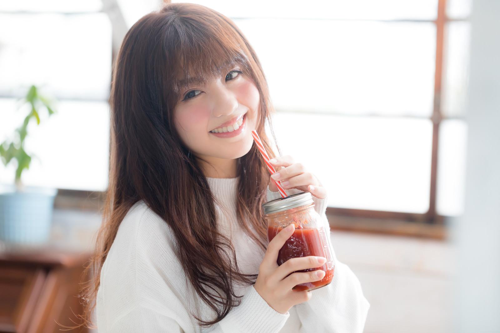 「レッドスムージーを飲む女性」の写真[モデル:河村友歌]