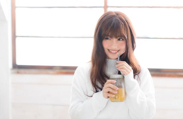 笑顔でスムージーを飲む女性の写真