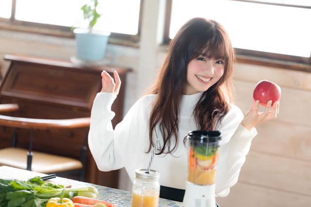 片手に赤い林檎を持った健康志向女子の写真