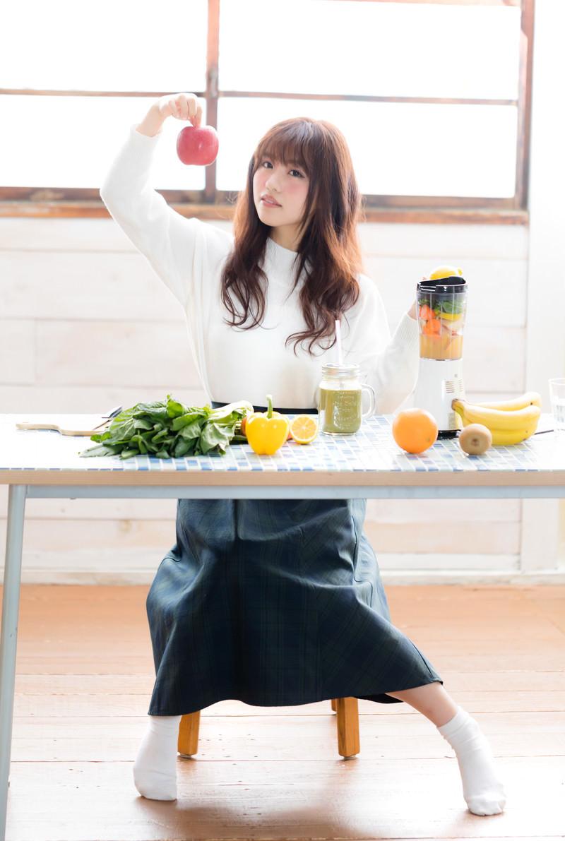 「林檎をスムージーにするか迷う女性」の写真[モデル:河村友歌]